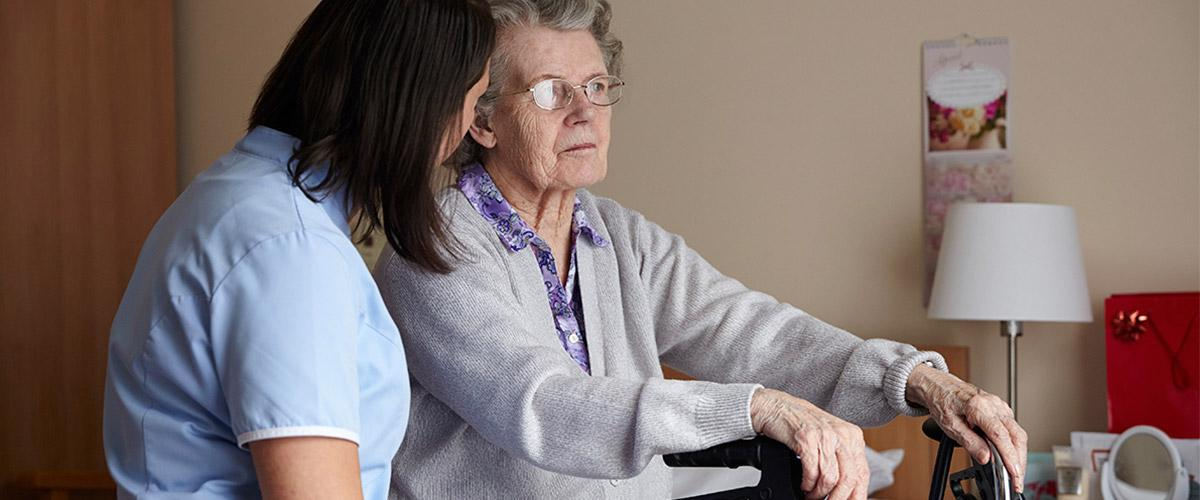 a fully trained care nurse sitting with a resident in her bedroom