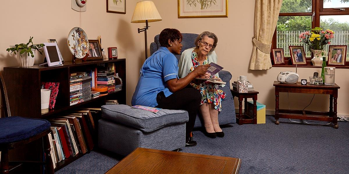a nurse sitting with a resident in her bedroom